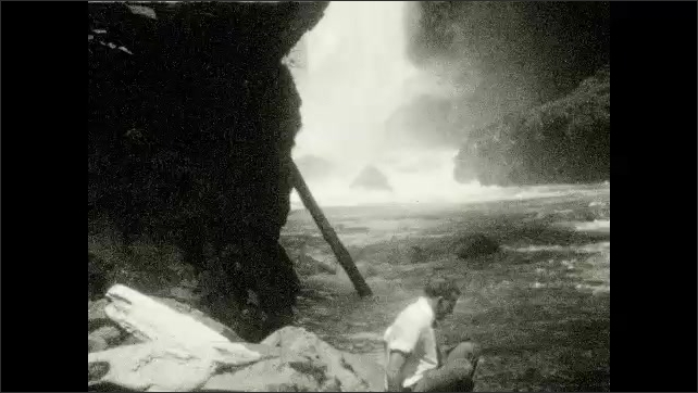 1920s: UNITED STATES: man kneels by waterfall. Man climbs down ledge by water. Man poses for photo by waterfall.