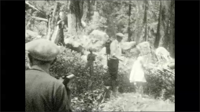 1920s: UNITED STATES: girl stands by waterfall. Waterfall in woods. Girl holds bracken leaf. Man and girl walk in woods. Man carries girl to rocks by waterfall.