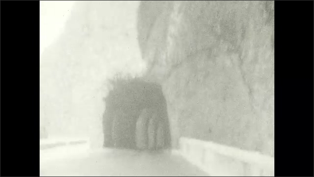 1920s: UNITED STATES: man hand feds animal. Car drives through tunnel. View along road.