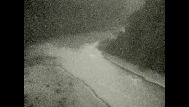 1920s: UNITED STATES: view of river in woods. River runs through gorge in mountains. Car drives over bridge in forest.