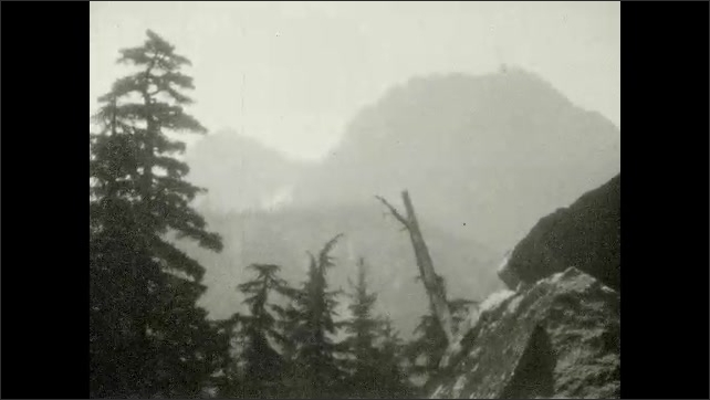 1920s: UNITED STATES: waterfall in woods. View across river to mountains. Man stands by waterfall.