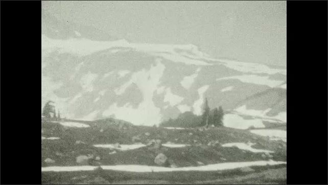 1920s: UNITED STATES: snow in mountains. Ridge on mountain. Family on mountain walk.