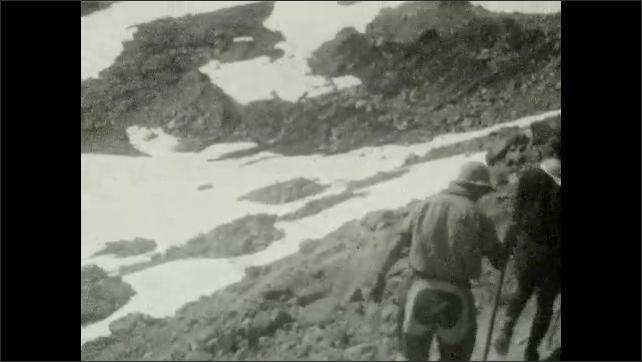 1920s: UNITED STATES: climber sits on rocks on mountain. Snow on mountain.