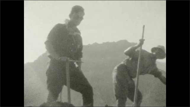 1920s: UNITED STATES: climber jumps on rock. Man in climbing goggles. Man with ice axe. Man hits ice with axe.