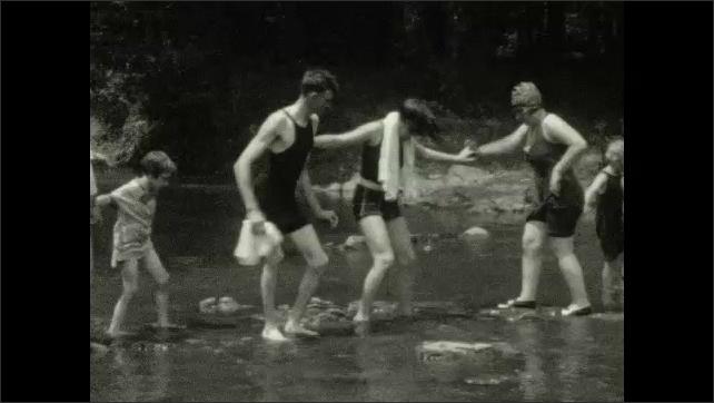 1930s: People playing in river. People walking on bridge. People in field. People on riverbank. Women posing in river. People playing on riverbank.