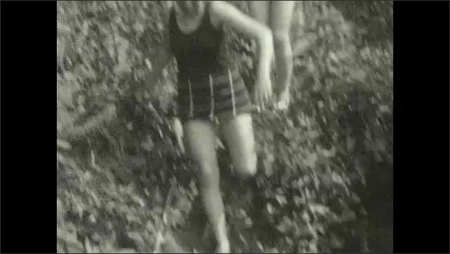 1930s: Tilting shots, women and girl in river. Women and girls posing in river. Women climb down hill. Women on shore. People swimming. Women dancing on bridge. Women pose with towels.