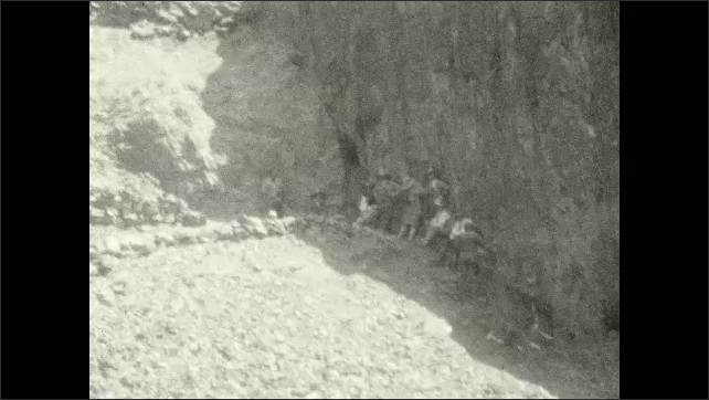 1920s: Man walks on a canyon trail, cliffs. Colorado River. Mule walks on a trail next to Kaibab Bridge. People stand in the shadow, canyon. People sit by mountainside.