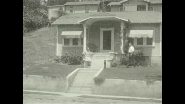 1920s: People stand in the front yard of a house, a girl walks around, a car is parked by the road. Woman and man walk in front of a house. The face of a man who talks. Two men smile and talk.