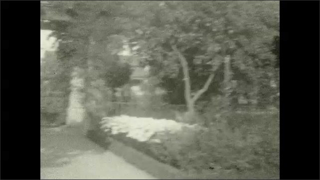 1920s: A girl stands next to flowers and talks in a garden. A garden, people walk. Daisies. Plant.