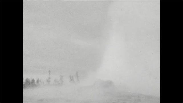 1920s: UNITED STATES: people watch Old Faithful geyser erupt. Water and spray above geyser. Family leave geyser. Man holds child's hand.