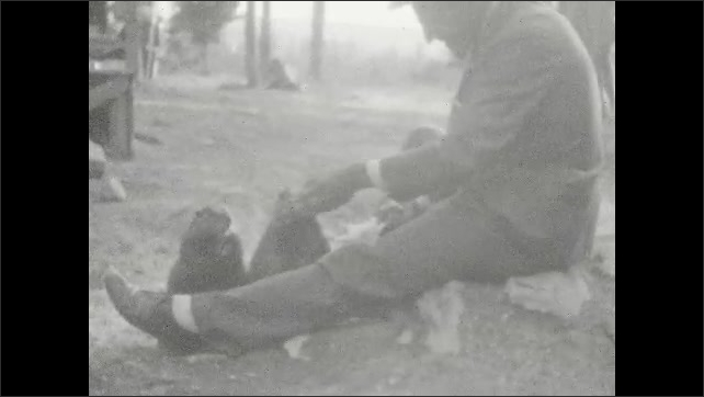 1920s: UNITED STATES: man feeds animals by hand. Man sits on ground. Close up of marmot. Lady and girl walk across bridge.