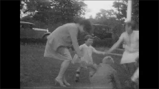 1920s: Teenage girl dances on lawn. Woman looks out from window of house. Girl and children play ring around the roses. Children roll on lawn. Teenage girl dances on lawn.