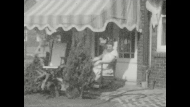 1920s: Woman stands near birdbath on lawn. Woman rocks in chair on porch. Man splashes water in birdbath. Boy rides bike through busy schoolyard.