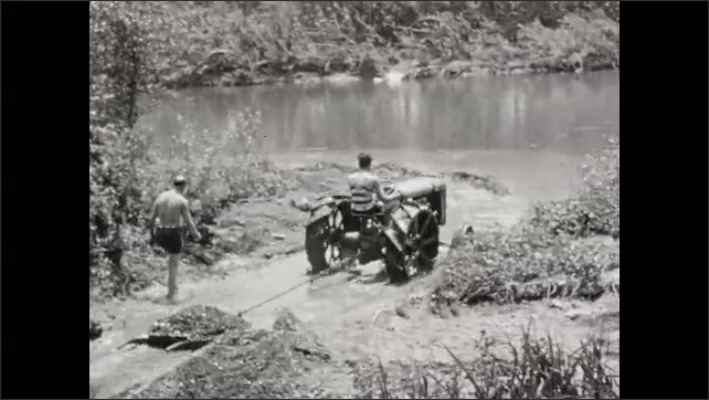 1930s: Man drives tractor through creek, tows object behind tractor. Man pushes pallet behind tractor.