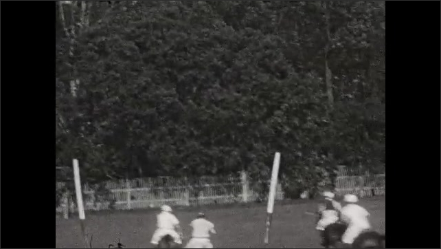 1930s: People play polo. Cars parked outside polo field.