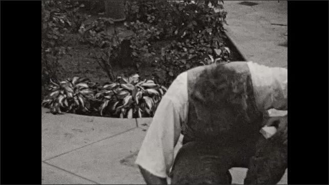 1930s: Woman holds baskets, dances a little. Women laugh, walk away. Man scrubs path. Man splashes water into bucket, pours water back into birdbath.