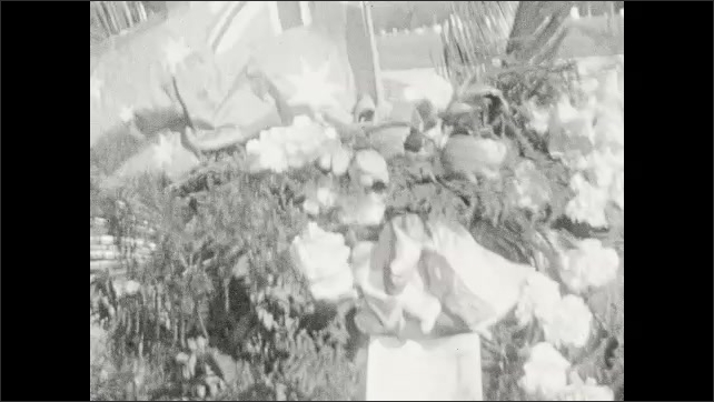 1920s: UNITED STATES: lady looks up at camera. Lady smiles at camera. Flowers at memorial service. People attend memorial event. Flags and flowers at ceremony