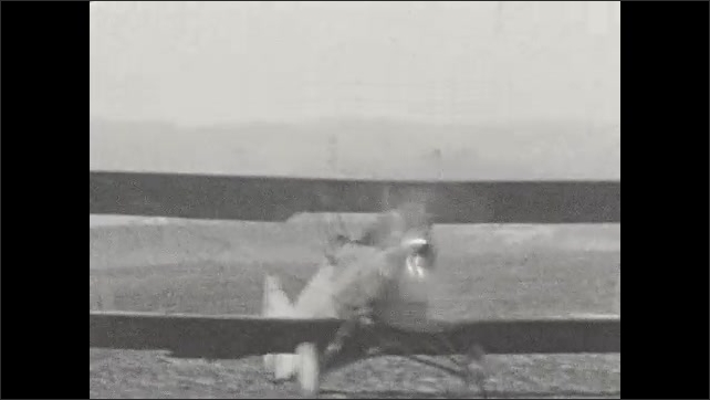 1920s: UNITED STATES: small plane in sky. Plane lands on grass. Propeller on plane. Plane drives over mud.