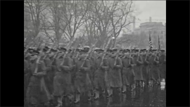 1920s: UNITED STATES: soldiers march with rifles in parade. Men play snare drums in parade. People watch military parade in street.