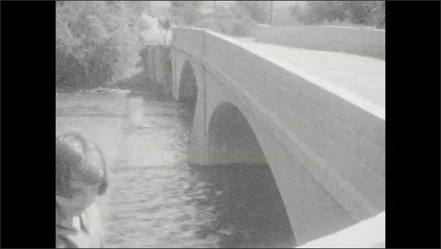 1920s: UNITED STATES: bridge across river. View from driver's seat of car. Fast flowing water under bridge. Flooded river. Girl looks at river from bridge.