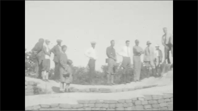 1930s: Canyon.  People climb ladder.  People stand on overlook.  Parked cars.