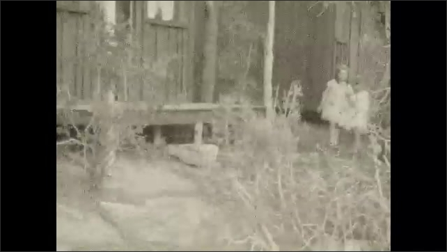 1930s: UNITED STATES: man on porch of log cabin. Girls on porch of cabin. Girl sits on porch with parents.