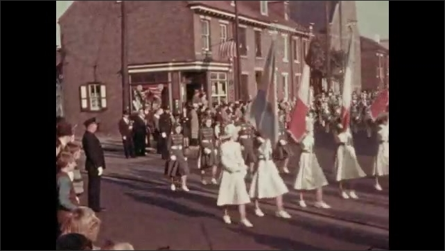1930s: Women march down street, carry flags. Marching band marches down street.