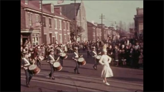 1930s: Men and women in uniform march in parade. Marching band marches in parade. Cars drive down street in parade.