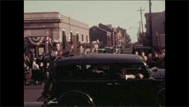 1930s: Boys and girls march in parade. Car drives down street in parade. Boy rides bicycle next to car. Dog rides on top of car.
