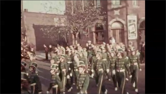 1930s: Children in band uniform march in parade. Children in uniform with instruments march in parade.