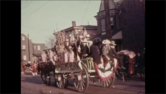1930s: Horses pull wagon with people. People wave American flags. Men stand behind sign.