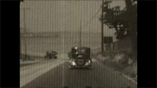 1930s: Tracking shots from car, driving by ocean. Shots of driving on road. Driving through city.