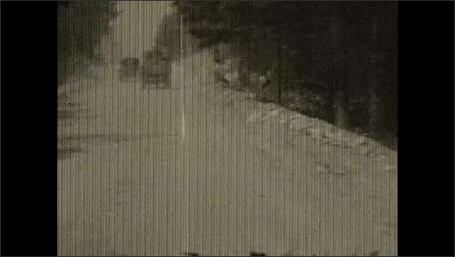 1930s: Tracking shots from car, driving across bridge. Driving on country road. Driving through town.