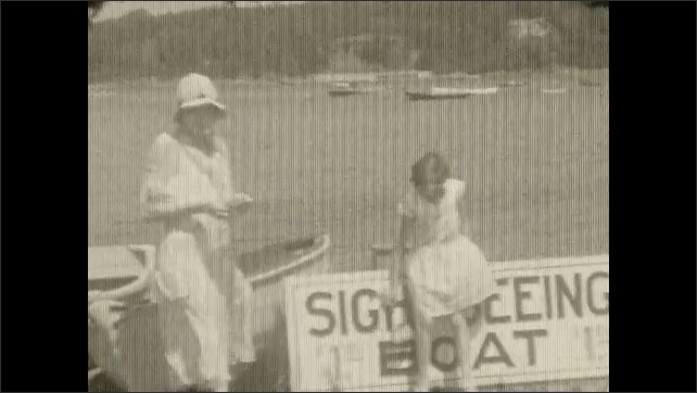 1930s: View of water from boat, flag waving. Woman and girl on pier. Girl walks past camera. Woman and girl next to boat.