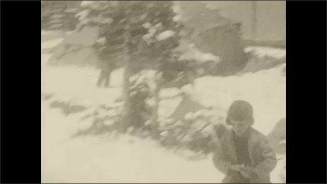 1930s: UNITED STATES: car drives along road in snow. Girl throws snowball at camera. Rear view of car on road.