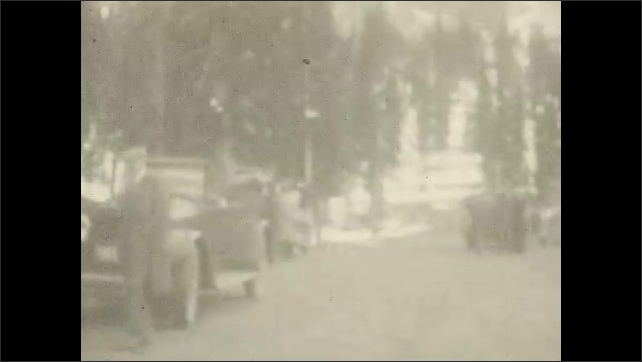 1930s: UNITED STATES: view of road from car window. Man puts hand over eyes. Go in Low Gear sign. Trees on mountain.