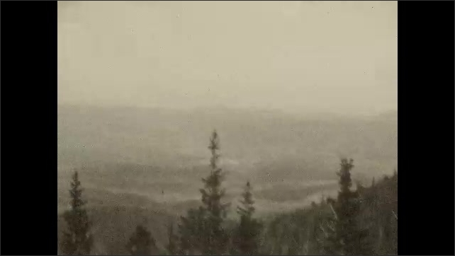 1930s: UNITED STATES: girl gets into car. Girl waves t camera. Snow on mountain. Forest in mountain. Car drives along track through mountains