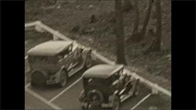 1930s: Man stands and waves.  Cars in parking lot.  Hills.
