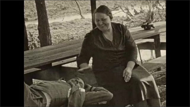 1930s: Picnic table.  Woman sits.  Man lays on bench.  Dog plays.  Woman rubs man's face and tickles chest.
