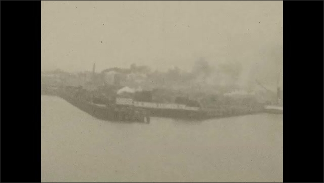 1930s: UNITED STATES: boats at sea. View of industry along coastline. View of docks. Lady leaves building with sack.