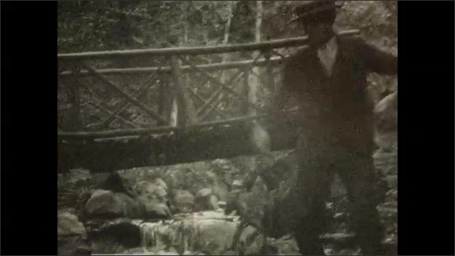 1920s: CANADA: man stands on footbridge in forest and waves. Man jumps over rocks.