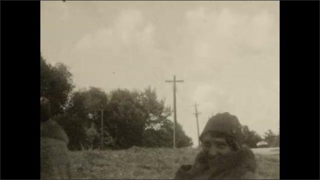 1920s: CANADA: ladies walk away from boat house by water. Lady smiles at camera. Girl smiles at camera. Man walks towards camera.