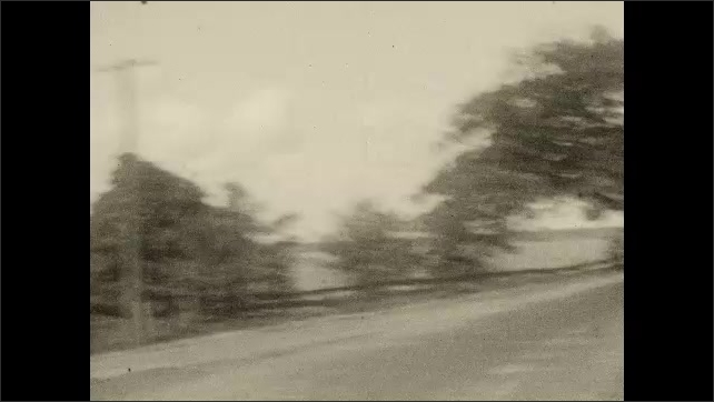 1920s: CANADA: view along road through window of car. Girl sat in car. Girl pulls faces. Lady smiles.