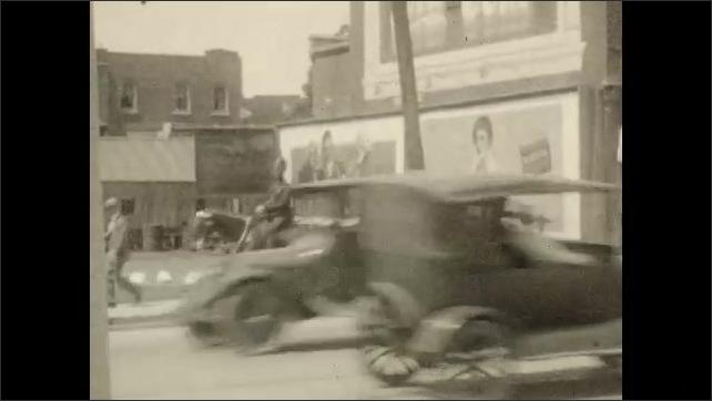 1920s: CANADA: ladies sit in car. Lady smiles at camera. Girl in car. Police man in street. Children run towards park.