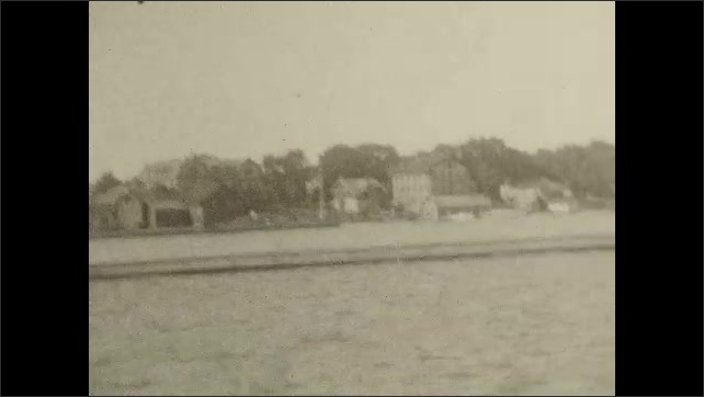 1920s: CANADA: canoe on water. Family lean over railing on boat. Ladies on deck of ship. Boat comes in to harbour. Settlement by water