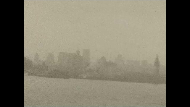 1920s: Boat travels across water. Man, woman and child sit on deck of boat. Skyline.