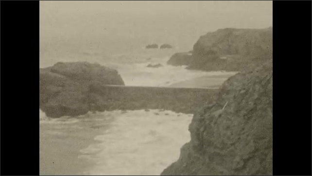 1920s: Rocks in ocean. Waves crash against rocks. Girl runs. Coastline and town.