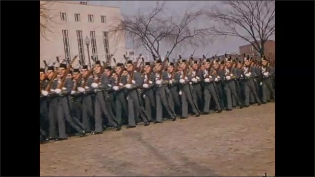 1950s: Color guard and marching band march in parade. Drill team marches in parade. Float drives through parade. Women march.