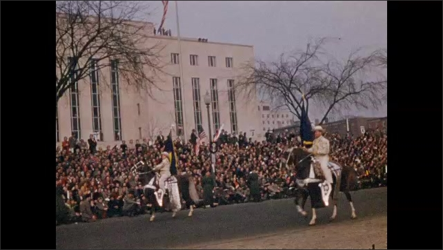 1950s: Horses march in parade. Men on horseback with flags in parade. Drum major throws baton in air and catches it.
