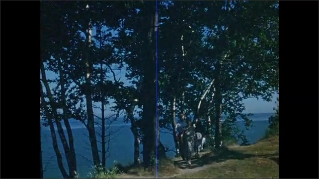 1950s: People walk on dirt path at scenic overlook.
